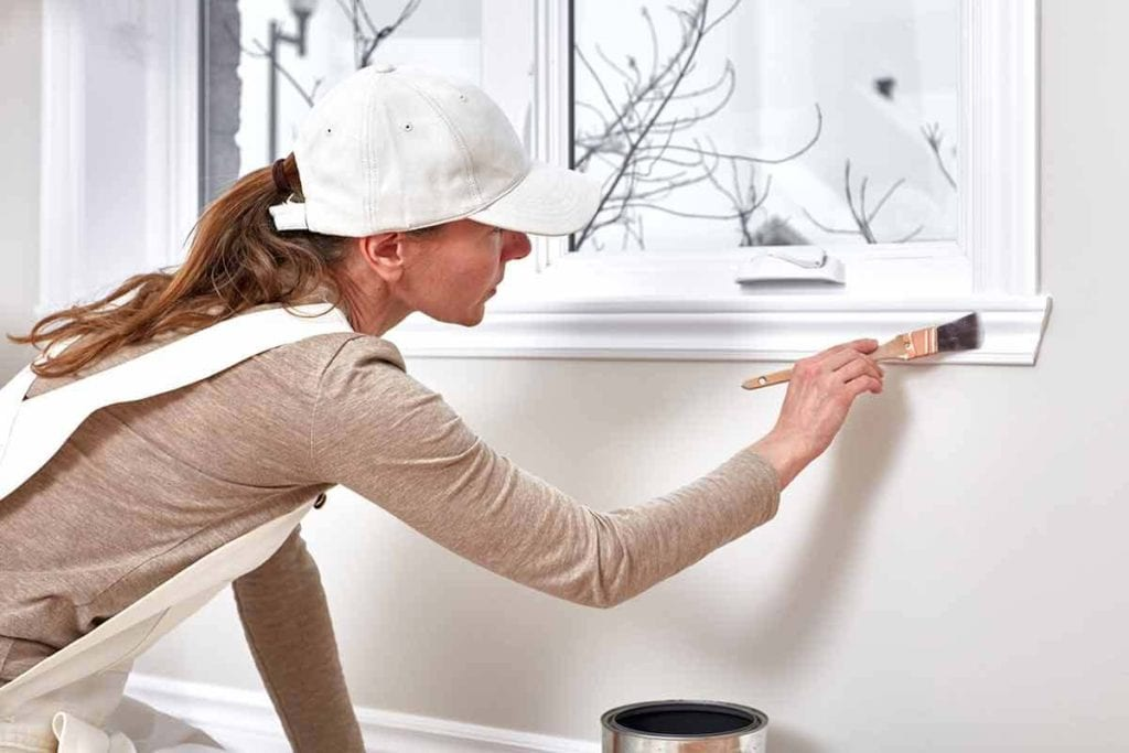 woman painting window trim with-oil based paint